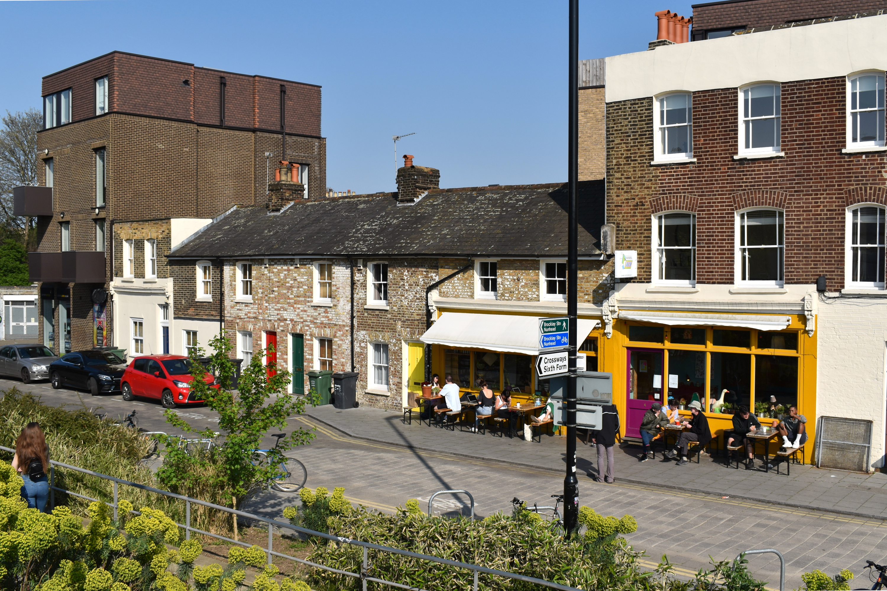 row of coffee shops with people sitting outside in sun