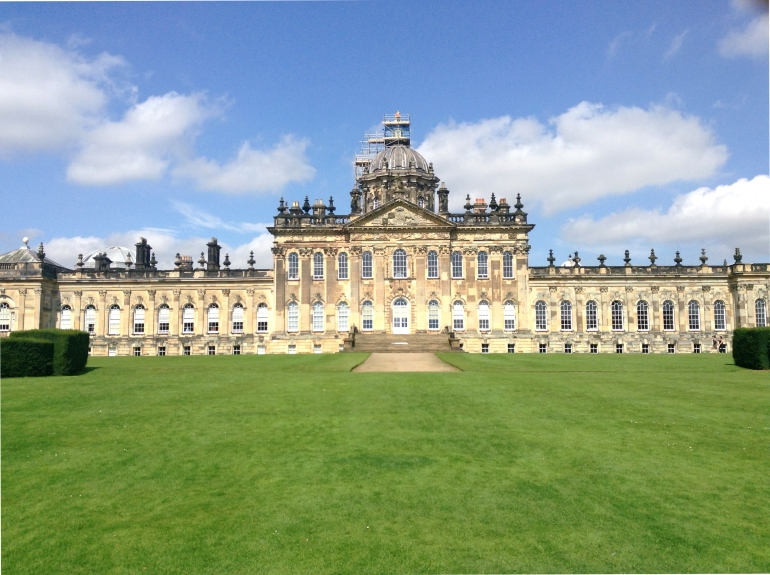 view of massive stately home on sunny day in front of grass gardens