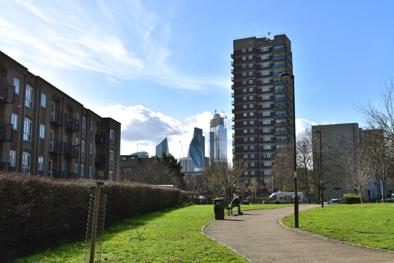 view of skyscrapers in city from small green park with man on bench and tower block