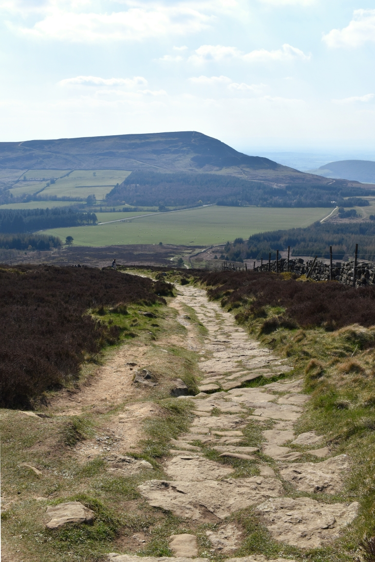looking down stone flagstones towards large hill with stone wall and heather