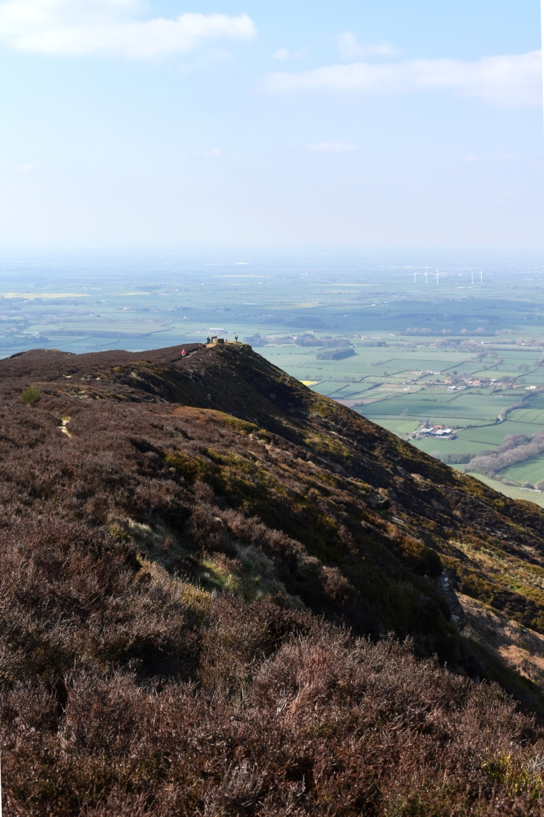 view of peak of a hill and countryside beyond with shadows of people