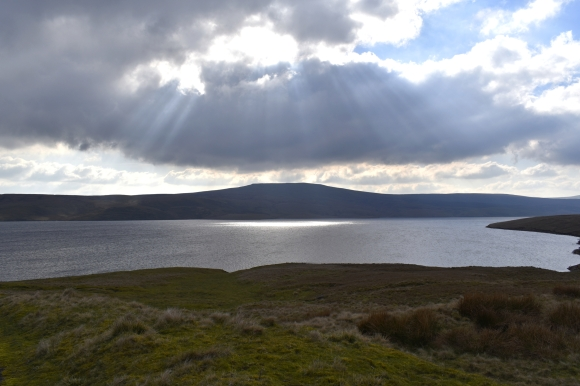 reservoir surrounded by hills with clouds and sunlight beams