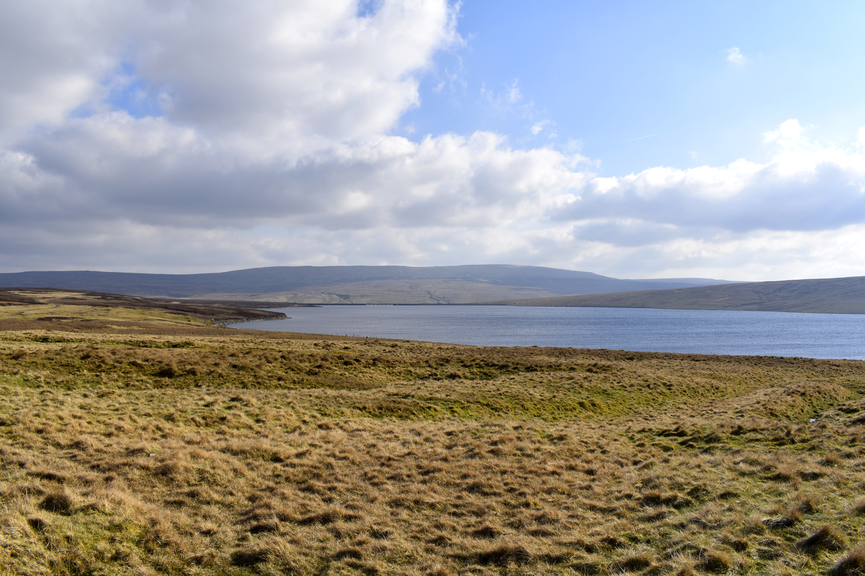 view of large reservoir with dam in the distance on a sunny day with clouds in the sky