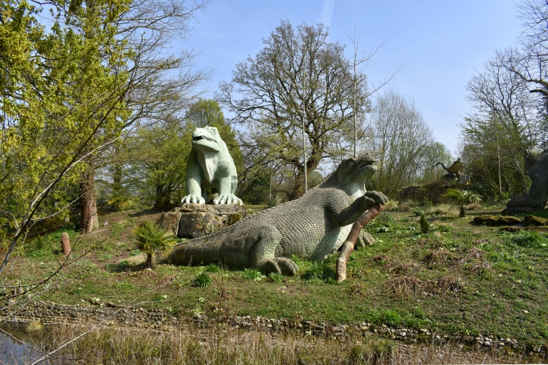 models of dinosaurs in park on sunny day green grass blue sky