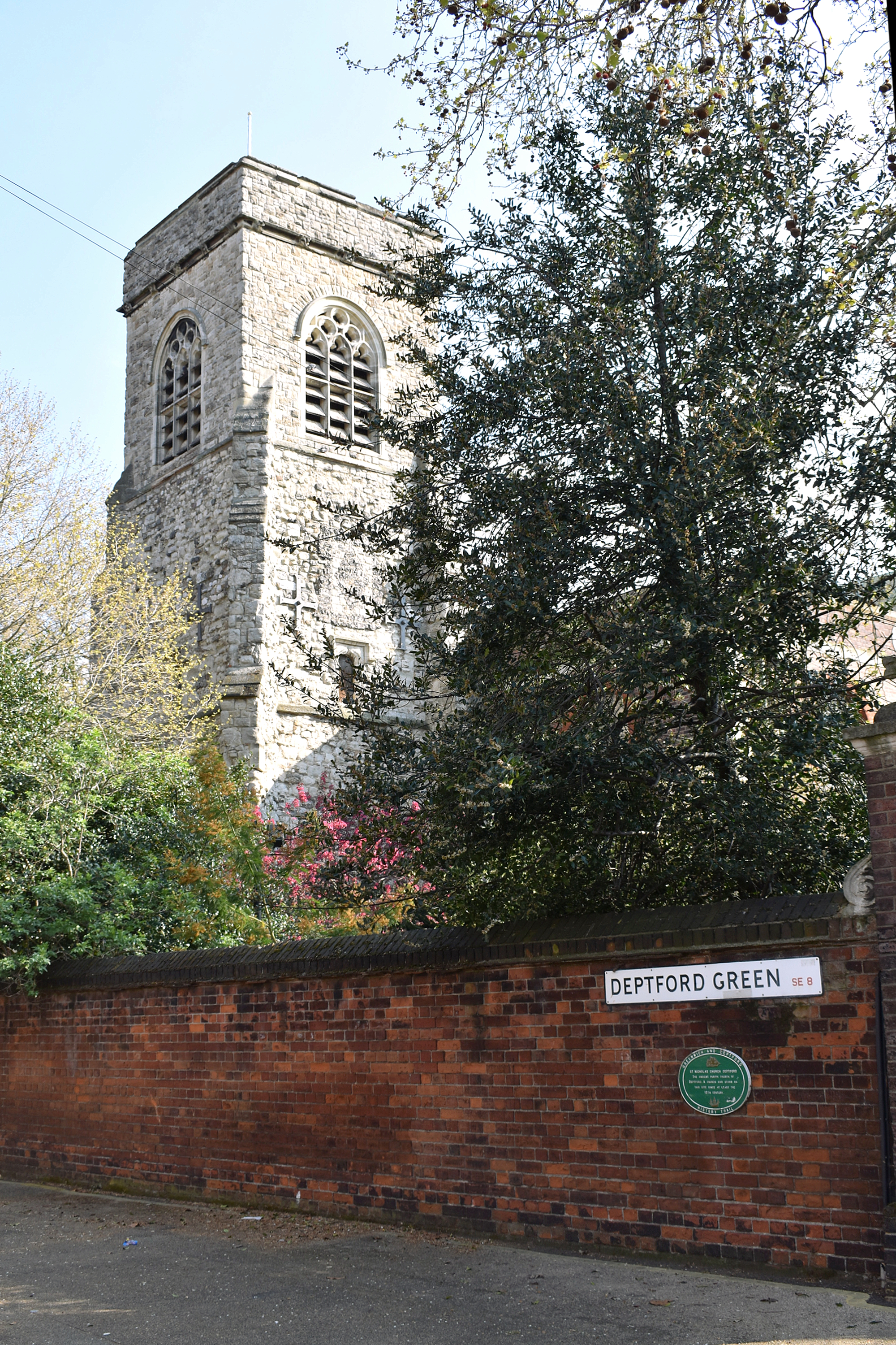 view of stone church tower behind trees