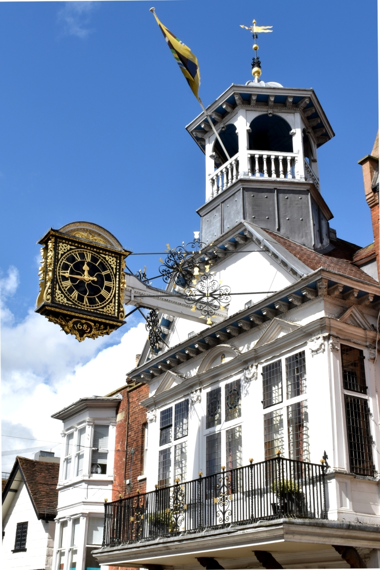 gold clock on old medieval building in town