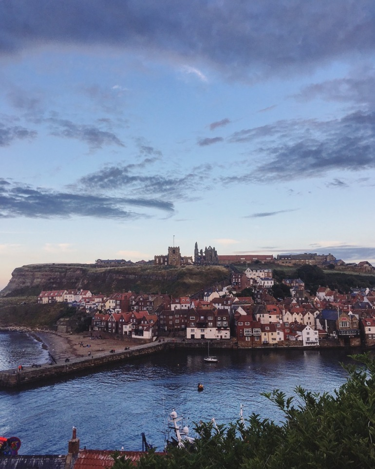 view of whitby abbey and old town with harbour at sunset
