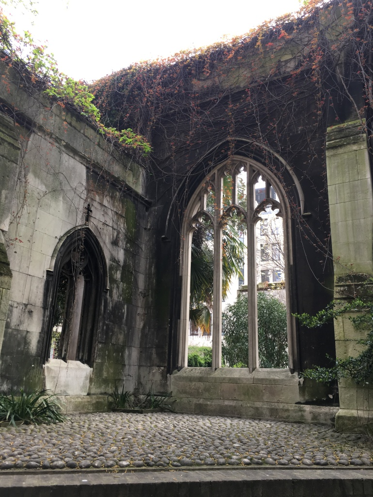 view of ruined church window with trees surrounding it and plants