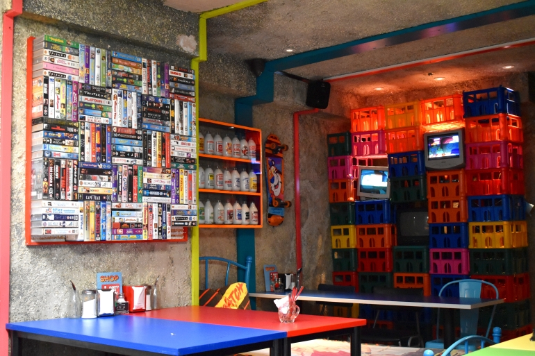 view of inside of cafe with cereal boxed and tables and chairs