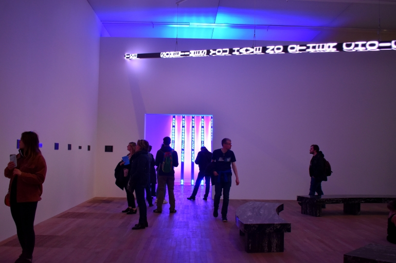 a room in an art gallery with neon art and people wandering