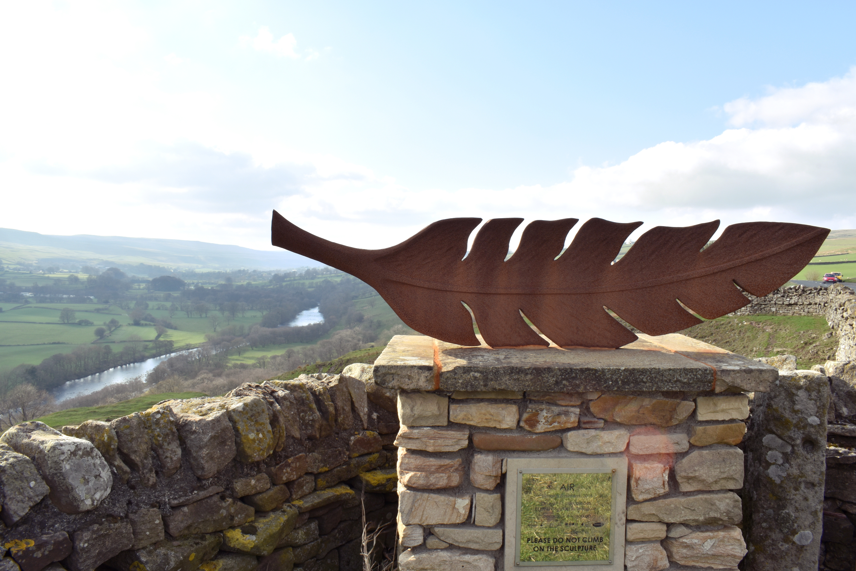 iron sculpture of a feather with river tees in the distance surrounded by hills