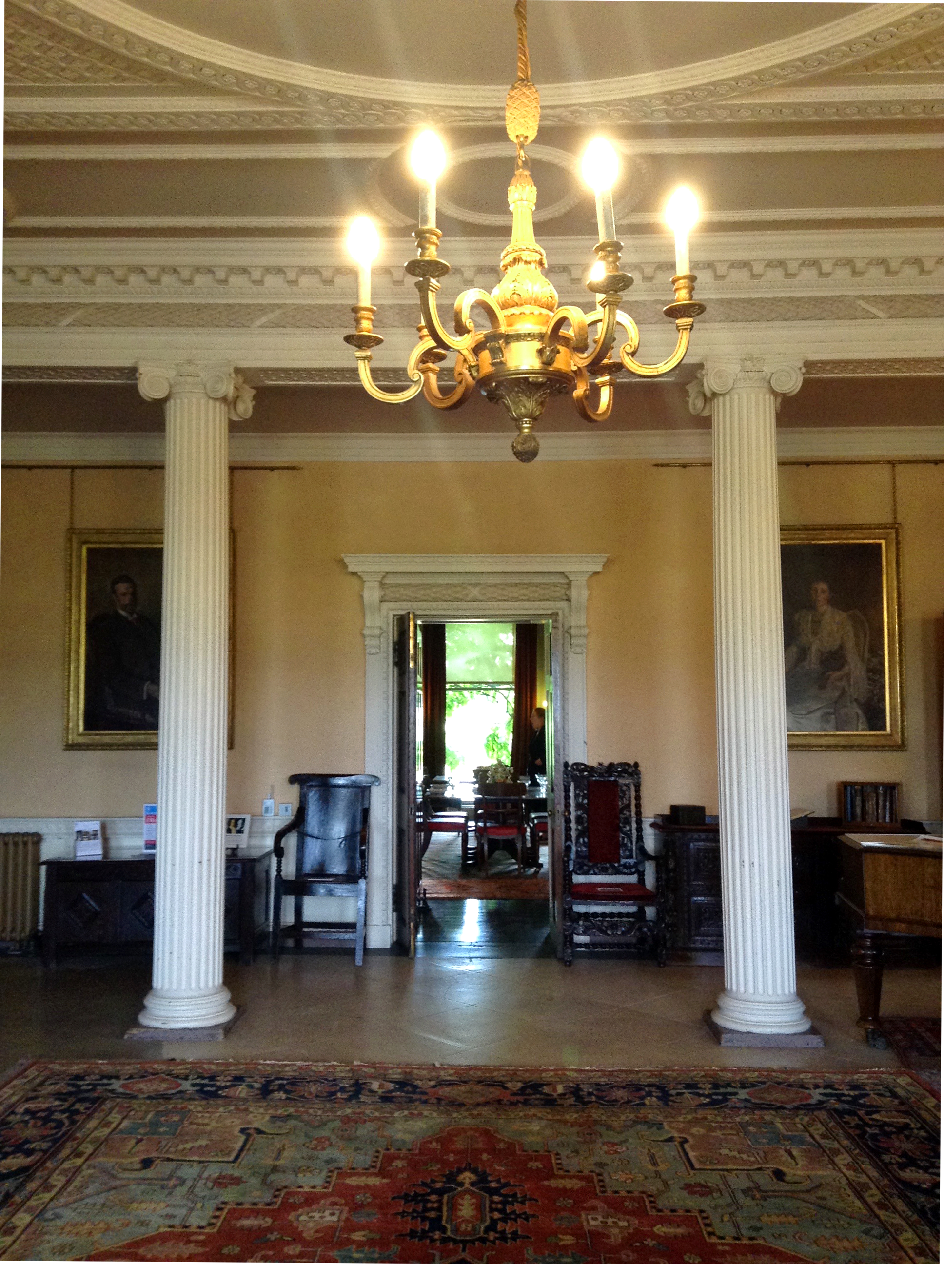 inside of a stately home with pillars and paintings and a chandelier in foreground