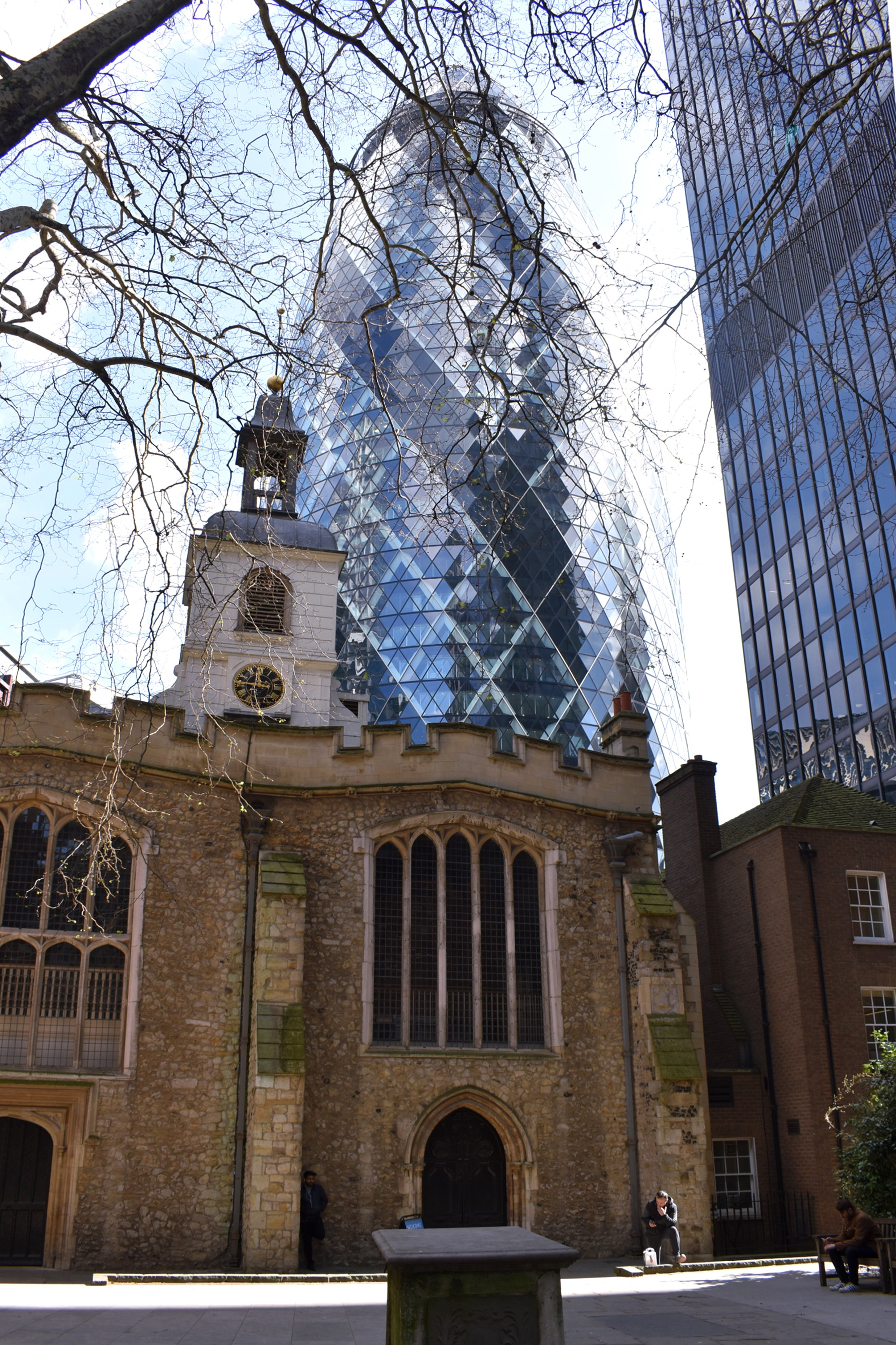 old church building in foreground with blue glass skyscraper behind