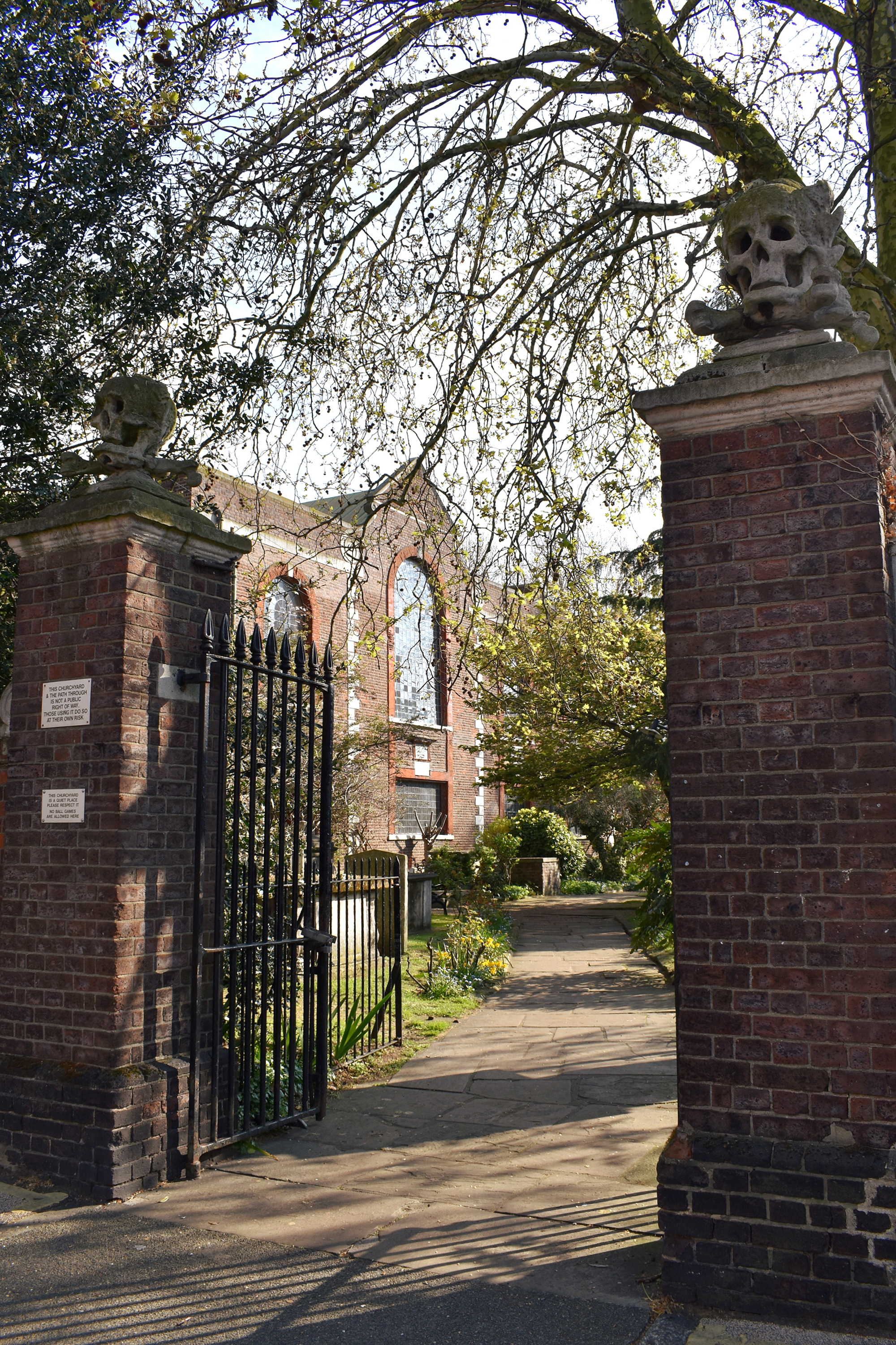 entrance gate to church with brick pillars and stone sculptures