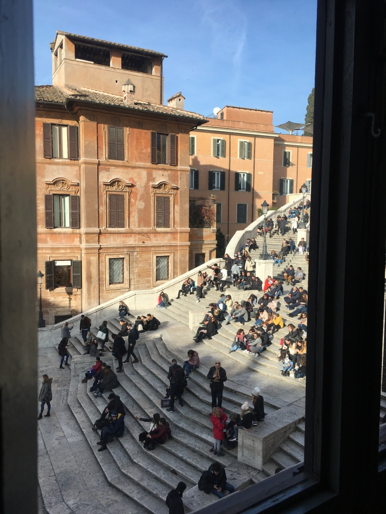looking out of window onto city steps in sun